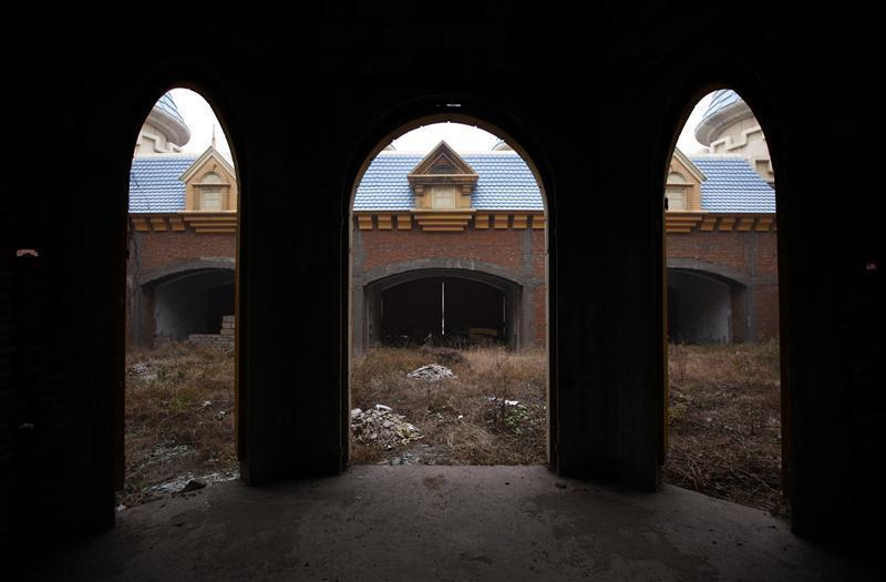 "ATTENTION EDITORS -- THIS IMAGE IS 8 of 18 TO ACCOMPANY A PICTURE PACKAGE ON AN ABANDONED AMUSEMENT PARK NEAR BEIJING. SEARCH KEYWORD ""WONDERLAND"" TO SEE ALL IMAGES PXP201-218. A view of abandoned buildings that were to be part of an amusement park called 'Wonderland', on the outskirts of Beijing December 5, 2011. Construction work at the park, which was promoted by developers as 'the largest amusement park in Asia', stopped around 1998 after funds were withdrawn due to disagreements over property prices with the local government and farmers. With local governments often dependent on land sales to fund payments on a staggering 10.7 trillion yuan ($1.7 trillion) of debt, Beijing worries that a collapsing property market will trigger a wave of defaults that in turn will hit the banks. More worrisome, the property market, which contributes about 10 percent of Chinese growth and drives activity in 50 other sectors, could drag the real economy to a hard landing. Picture taken December 5, 2011. REUTERS/David Gray (CHINA - Tags: REAL ESTATE BUSINESS SOCIETY CONSTRUCTION)"